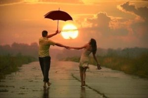 молодой человек и девушка под зонтом на закате